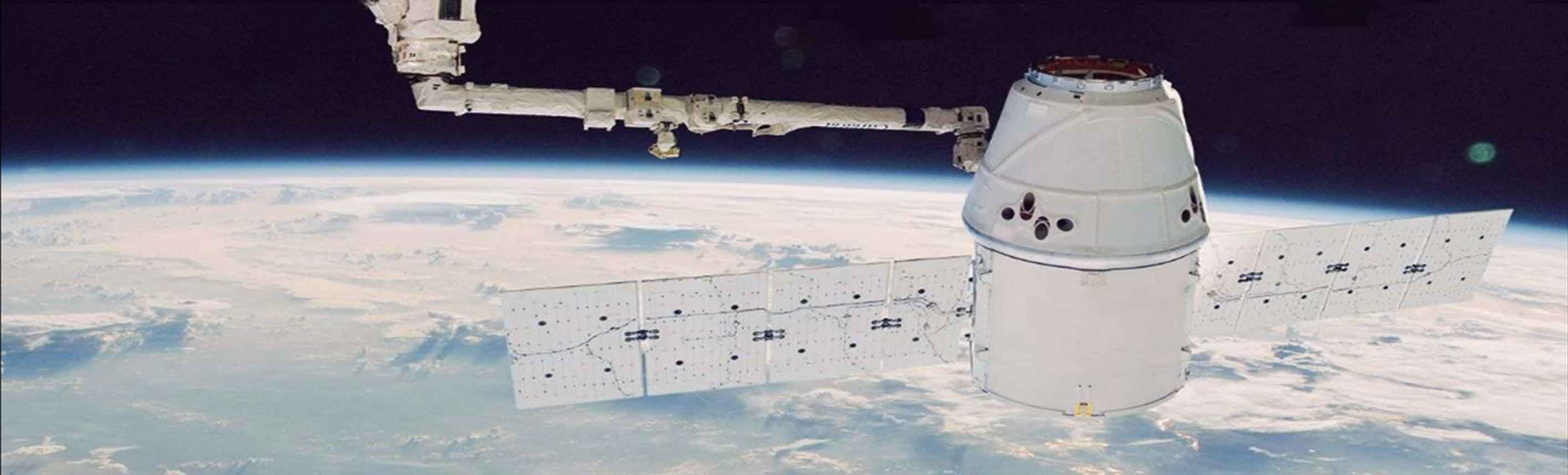 Image of space craft orbiting the earth with solar panels